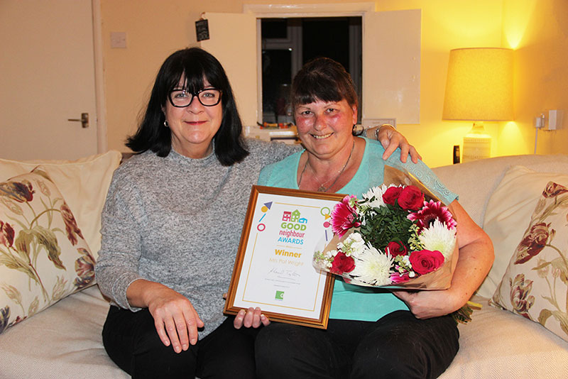 Nichola (left) presenting her good neighbour Pat (right) with her award